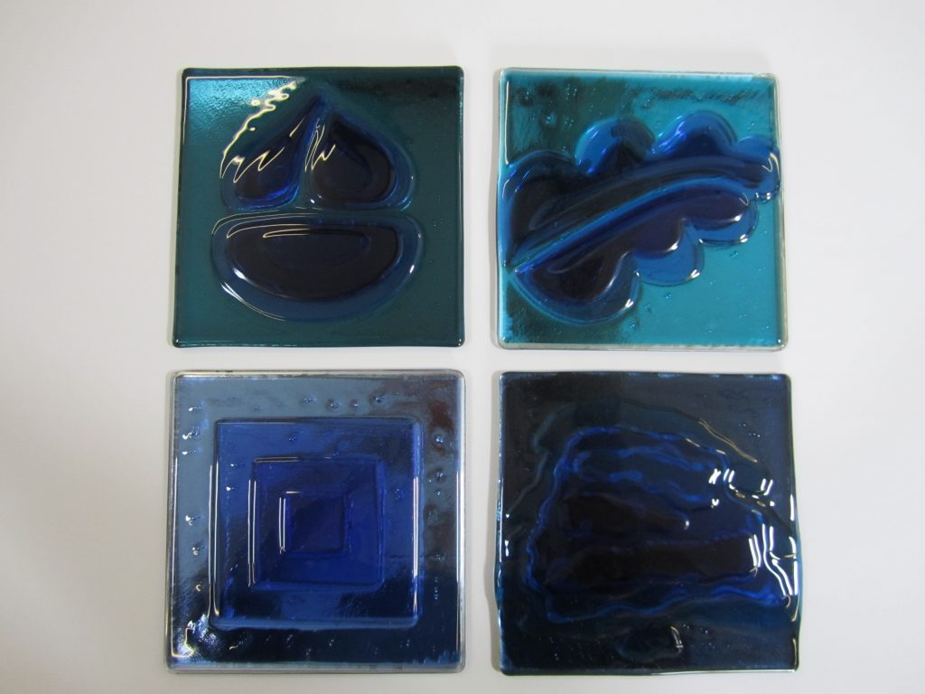 A set of four fused glass panels based on the companies logo