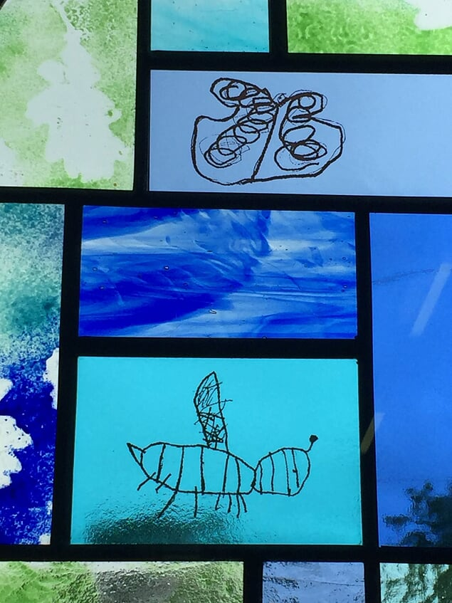 A detail showing some of the pupils drawings decalled onto the window at Chadlington primary school